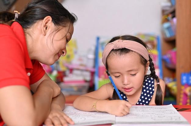 ホームスクールのコンセプト、アジアの子供たちと母親が学校の宿題を教える