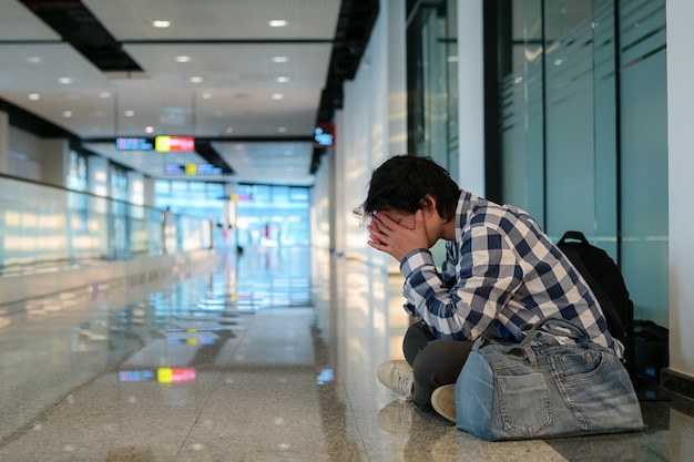 公共の道の方法で床に座っている男。彼は失業に適用することができなかったので彼は頭とバッグに手を握って苦痛とストレスを感じています