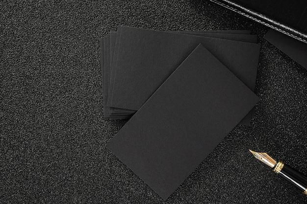 空の黒の名刺は、私たちの連絡先のデザインのテンプルテを使用するために黒の背景をモックアップ