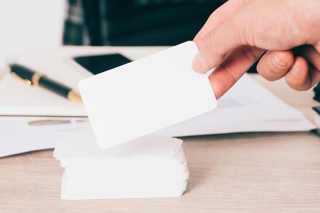 ぼやけたオフィスデスクの背景に手に空の名刺を使用して連絡先情報のデザインを模倣