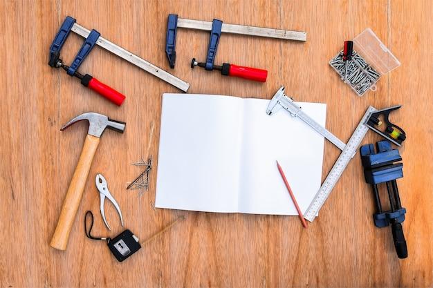Коллекция рабочих инструментов, набор рабочих инструментов. (стальной ключ, молоток, гвозди, болты, гаечные ключи и т. д.) с записной книжкой на деревянном столе.