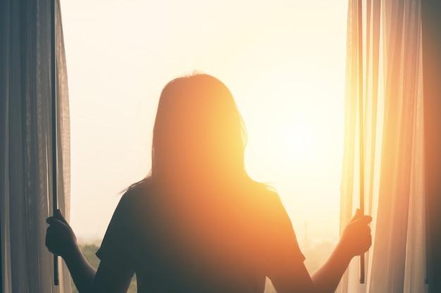 若い女性は寝室に立っているカーテンは目を覚ました後に日の出を見る