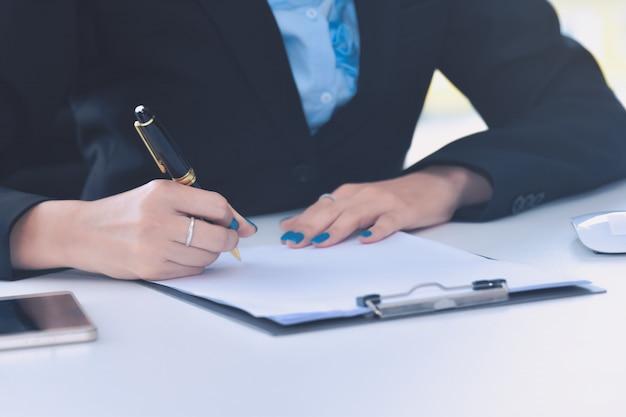 Закройте деловая женщина, подписав контрактный документ
