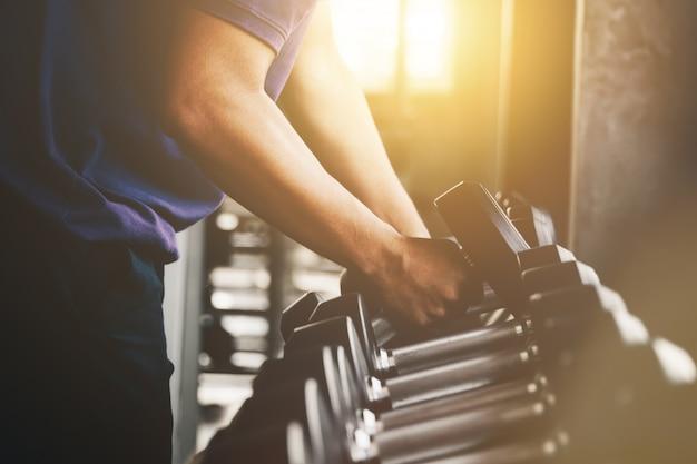 ジムで手を持つ重量のダンベルを閉じます金属のダンベルで腕の筋肉の運動を閉じます