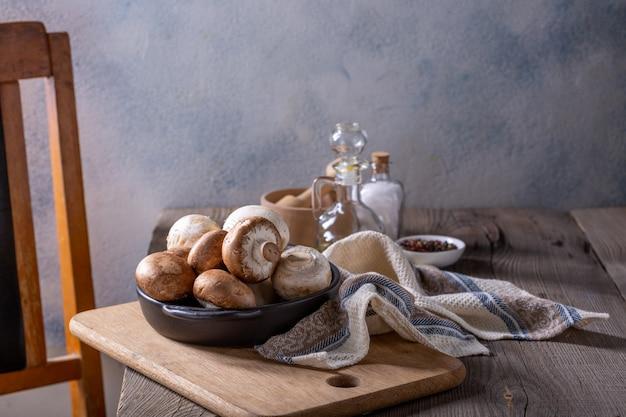 シャンピニオンキノコとスパイスの木製テーブル。料理のコンセプト