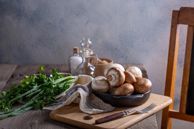 キノコ料理の準備のための製品。シャンピニオン、ディル、パセリ、ネギ、木製のテーブル。料理のコンセプト