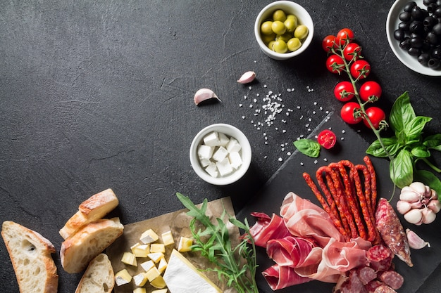 Концепция тапас. прошутто, колбаса чоризо, оливки, помидоры черри, руккола, базилик и сыр бри на черной грифельной доске. антипасти концепция.
