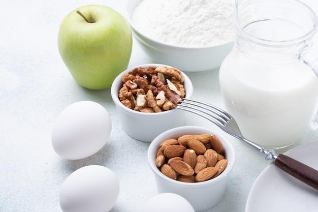 Молоко, мука, яйца, орехи и зеленые яблоки на деревянном столе. ингредиенты для яблочной шарлотки. рецепт блюда
