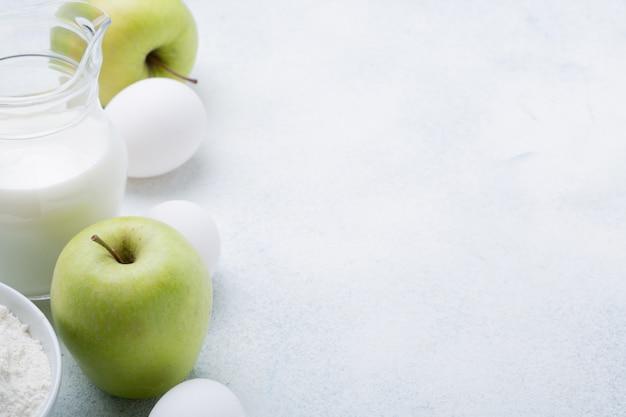 Молоко, мука, яйца и зеленые яблоки на белом фоне. ингредиенты для яблочной шарлотки. рецепт блюда