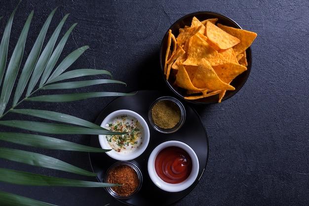 Традиционные мексиканские закуски начос в черной тарелке с различными соусами и пряные специи на фоне пальмовой ветви. черный фон.