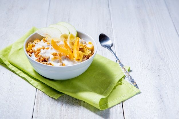 リンゴ、アプリコット、白い木製の表面にバナナのスライスとグラノーラとベジタリアンのヨーグルト。健康的な朝食のコンセプト