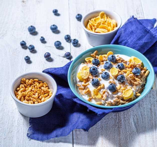 ヨーグルト、ボウルにグラノーラ、ブルーベリー、コーンフレーク、白い表面にパフライス。ヘルシーな朝食