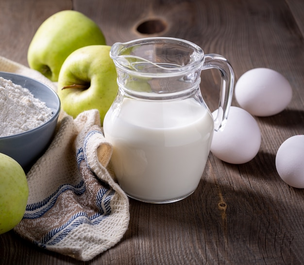 牛乳、小麦粉、卵、木製のテーブルに青リンゴ。アップルシャーロットの材料