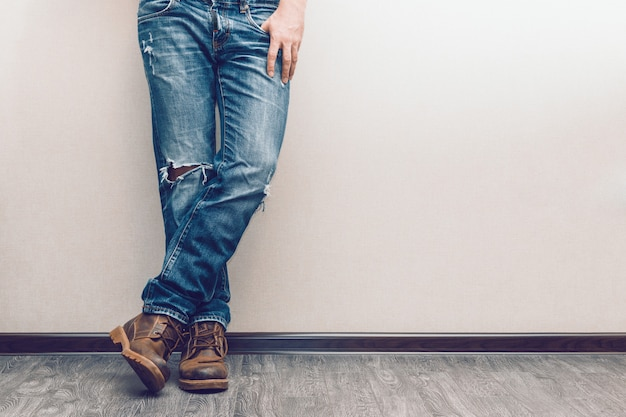 Молодые модные мужские ноги в джинсах и сапогах на деревянном полу
