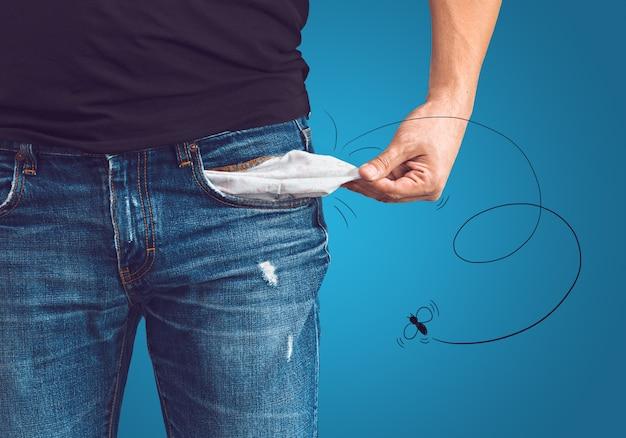 Бедный человек в джинсах с пустым карманом и нарисованной концепцией мухи