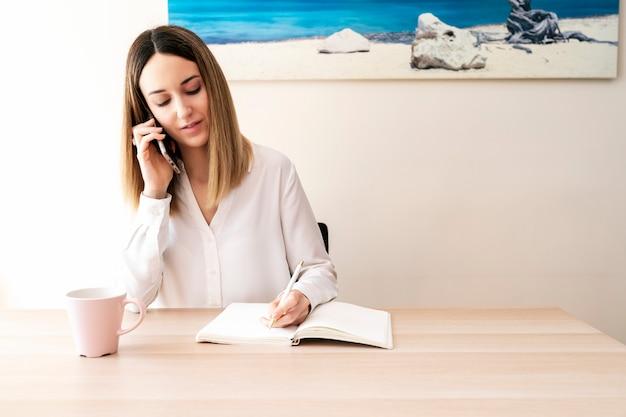 Молодая женщина имея звонок встречи и принимая примечания дома. оставайтесь дома, работайте из дома концепции.