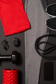 黒い背景に自宅やスタジオやジムでのトレーニングのための男性のトレーニング機器の平面図です。健康的なライフスタイルのコンセプト