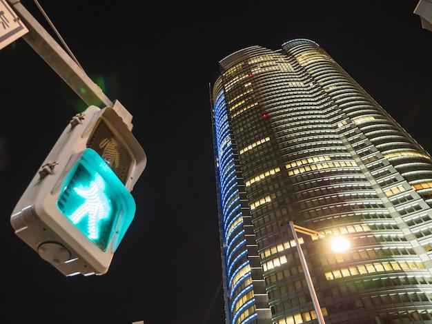 歩行者信号機と高層ビルの緑の色の広い視野