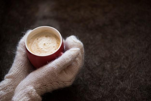 Восхитительный согревающий кофе в красном круге зимой в холодном виде в руках девушки в вязаных перчатках