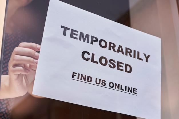 店やレストランの労働者が閉じた看板をぶら下げ