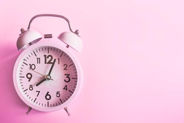 ピンクの上に横たわるピンクの目覚まし時計