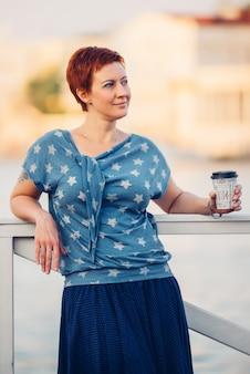 デニムブラウスとスカートの屋外のポートレートの桟橋に短い髪の美しい若い赤毛の微笑の女の子。