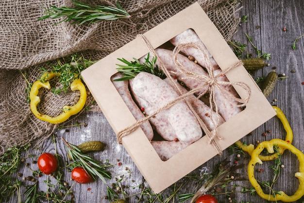 素朴なまな板のクラフトボックスで生の生肉ソーセージ。生肉ソーセージのタマネギ、ニンニク、タイム、ローズマリー、セージの葉、コリアンダー、ピーマンのスパイス。