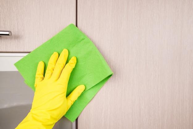 雑巾で木製家具を洗浄する保護手袋を手に。春先の清掃または定期的な清掃。メイドは家を掃除します。