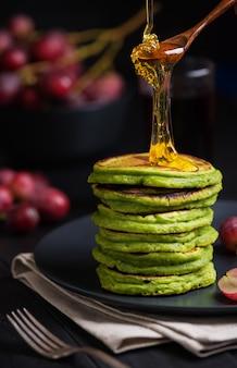 Зеленые блины с чаем из матчи или шпинатом, заправленные медом и красным виноградом. идеи и рецепты для здорового завтрака с супер-пупер ингредиентами. темный фон