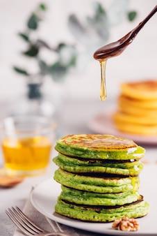 Зеленые блины с чаем из матчи или шпинатом, заправленные медом и красным виноградом. здоровый завтрак с суперпродуктами. светлый фон, огромный скандинавский стиль