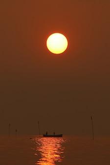 Парусник плывет по воде, на фоне оранжевого закатного неба в мирной безмятежной природе.