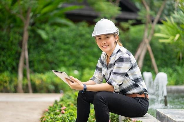 下水処理場でタブレットのラップトップで働くタイのアジアの女性工学