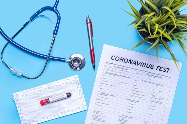 聴診器、植木鉢、ペン、フェイスマスク、試験管、コロナウイルス、青いフラットレイアウトの背景に文書のテストとウイルスの患者の健康診断と医療検査のレイアウト