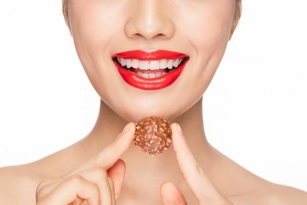 チョコレートの口のクローズアップを食べる女性