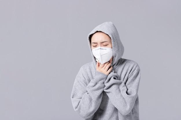 新しいコロナウイルスの概念。アジアの女性は鼻が詰まっているか鼻水があり、発熱があります。