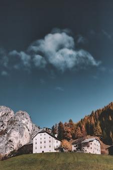 曇り空の下で山の横にある建物