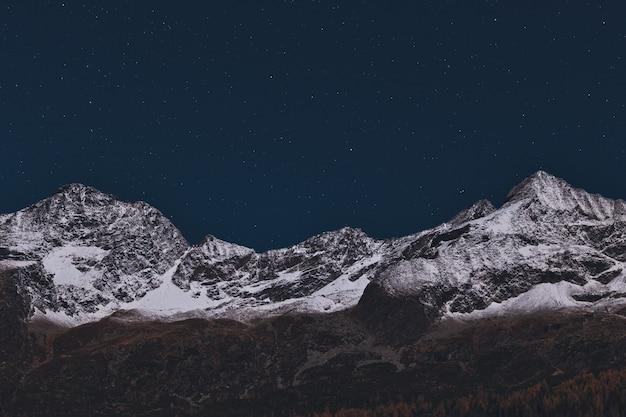 夜間に雪で覆われた山