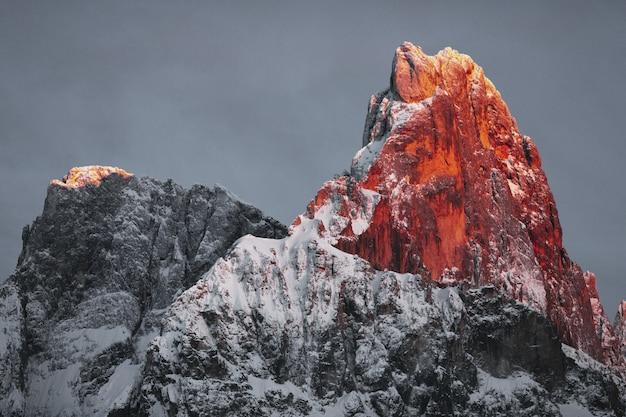 Снег покрыл скалистую гору под облачным небом