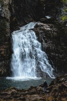Мужчина стоит возле водопада