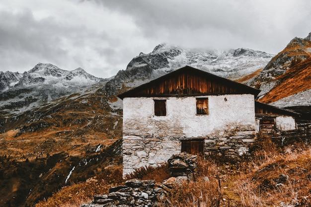 雪をかぶった山の近くの白と茶色の家
