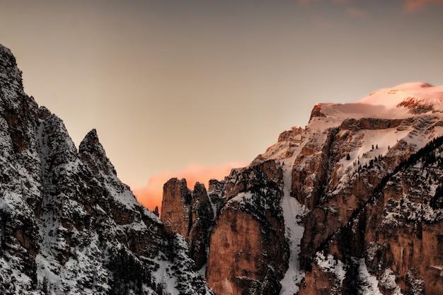 茶色と灰色の雪に覆われた山