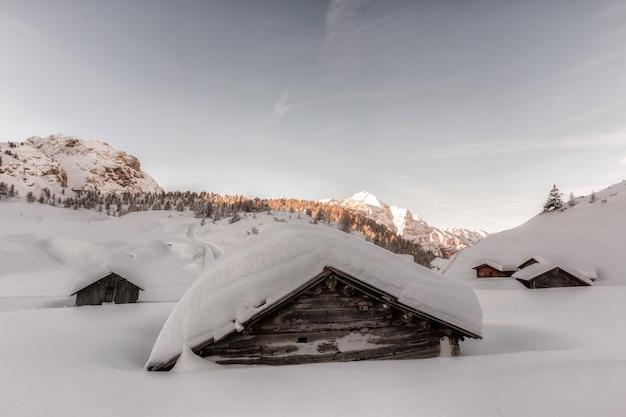 昼間は雪に覆われた茶色の木造住宅