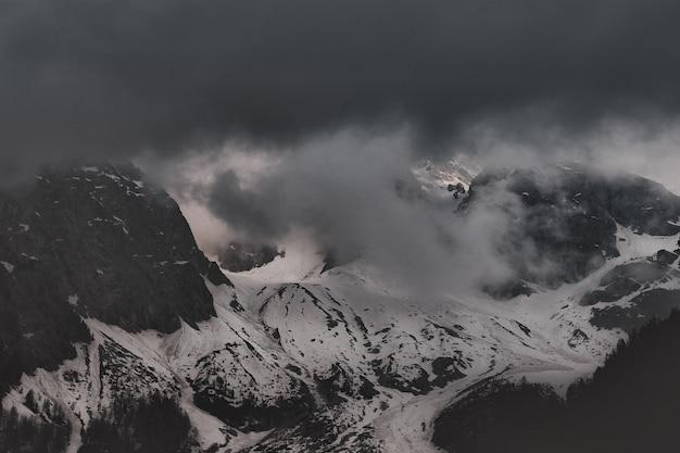 水の近くの雪に覆われた黒い山