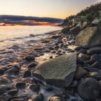 Серые скалы на берегу моря во время заката