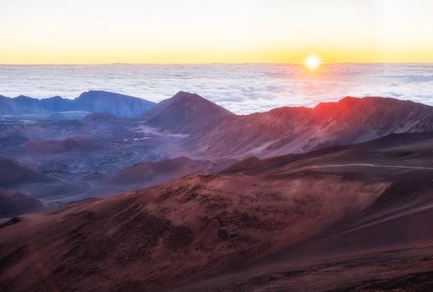 白い雲の下の茶色と白の山