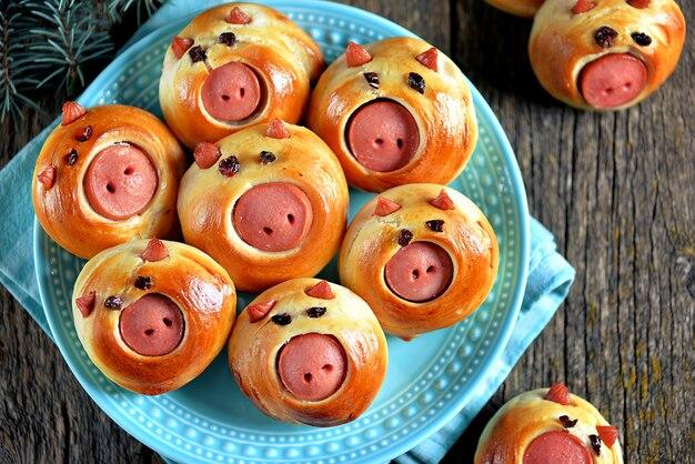 Милые свиные булочки с сосисками на тарелке