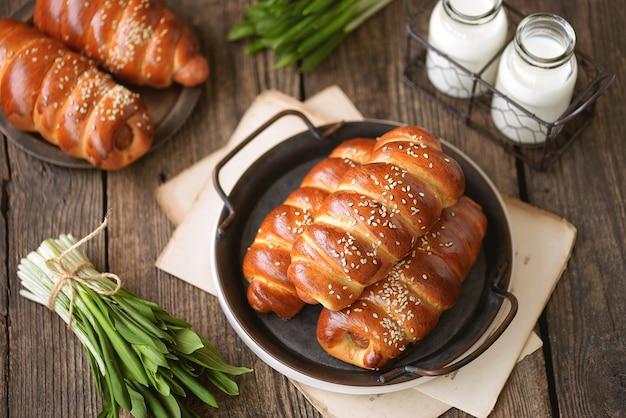Домашние колбаски в дрожжевом тесте с кунжутом и молоком на деревянной поверхности.