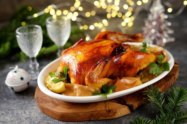 Вкусный жареный цыпленок с кусочками яблока. рождественская еда