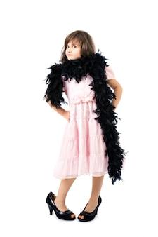 Маленькая девочка в туфлях на высоком каблуке и боа