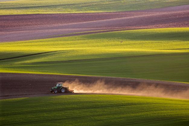 トラクターは春にフィールドを耕します